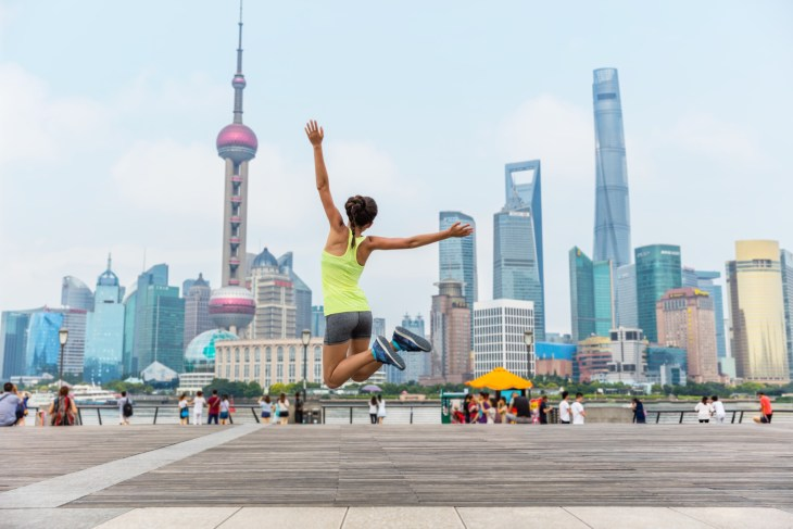 Young athletic Chinese woman jumping with Shanghai skyline in background