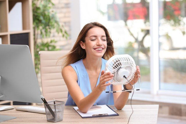 Businesswoman refreshing from heat with small fan at workplace