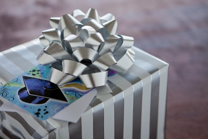 Gift with silver wrapping paper and bow and card with graduation cap on it