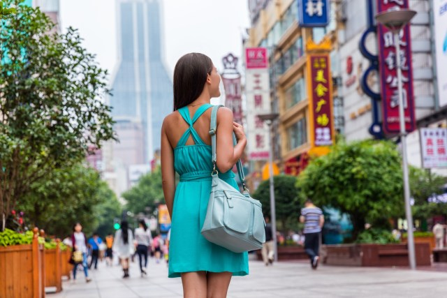 Brunette young woman with turquoise dress and purse exploring city