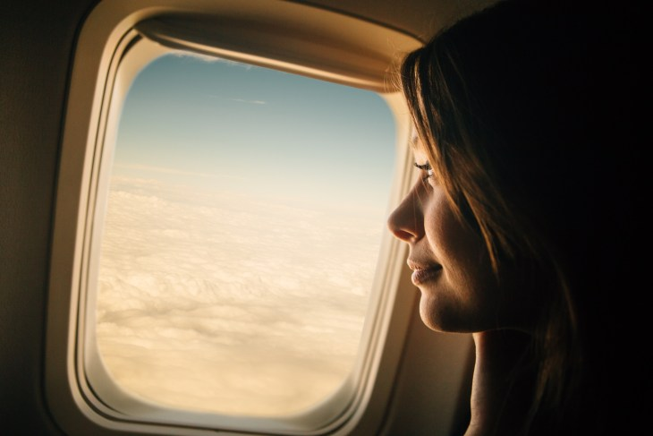 Young girl looking through window on an airplane