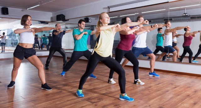 group of men and women in workout studio doing a zumba class