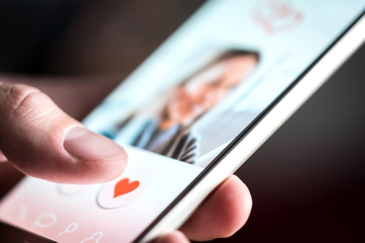A man swiping for an attractive woman on a dating mobile app.