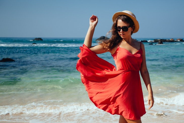 Brunette woman on the beach in red dress, sunglasses and straw beach hat