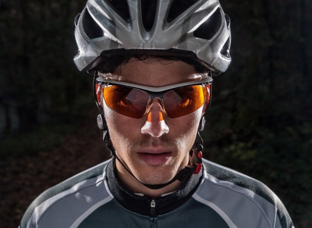A biker wearing the perfect cyclist shades to shield his eyes, while riding.