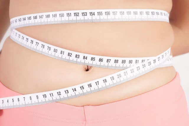 A girl measuring her waist size.