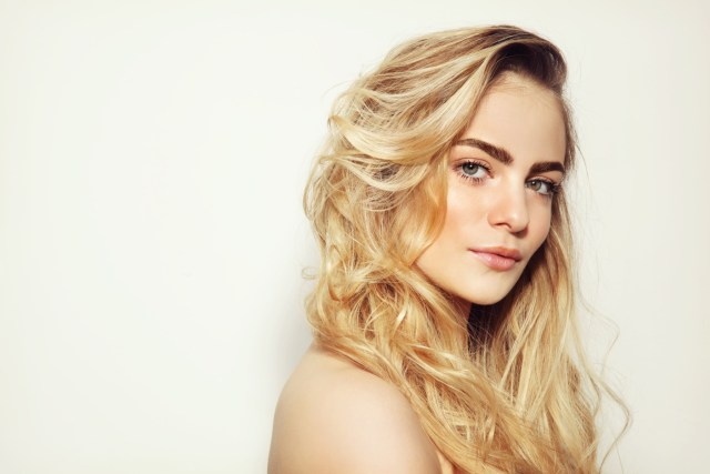 Profile of bleach blonde woman staring into camera