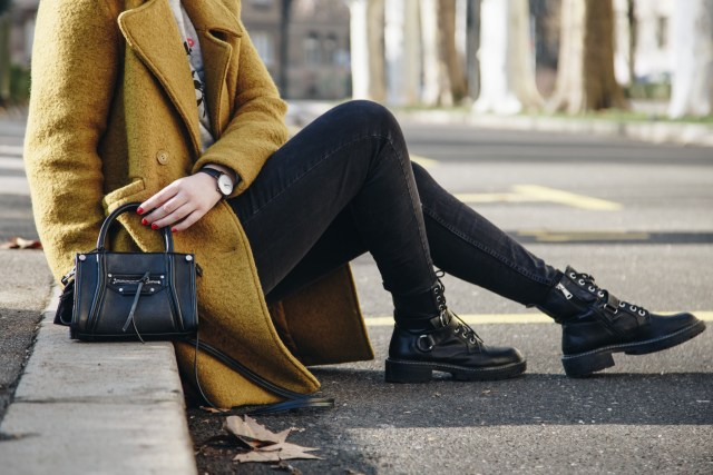 Woman with long pea coat wearing Doc Martens