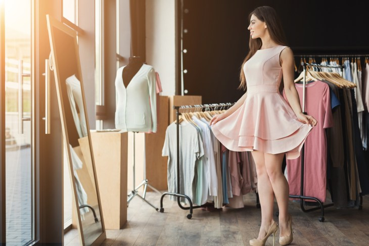 Woman trying on a dress in front of a mirror and many other dresses hanging next to her