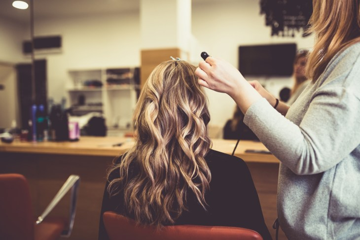 Girl with brunette hair and blonde highlights sitting with hairstylist