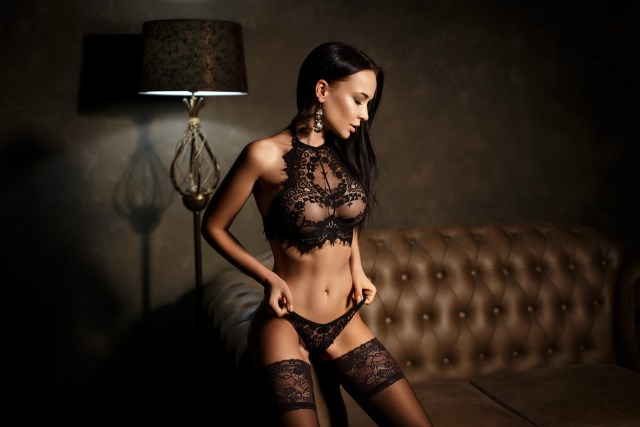 Woman wearing matching black lace lingerie set with halter neck bra