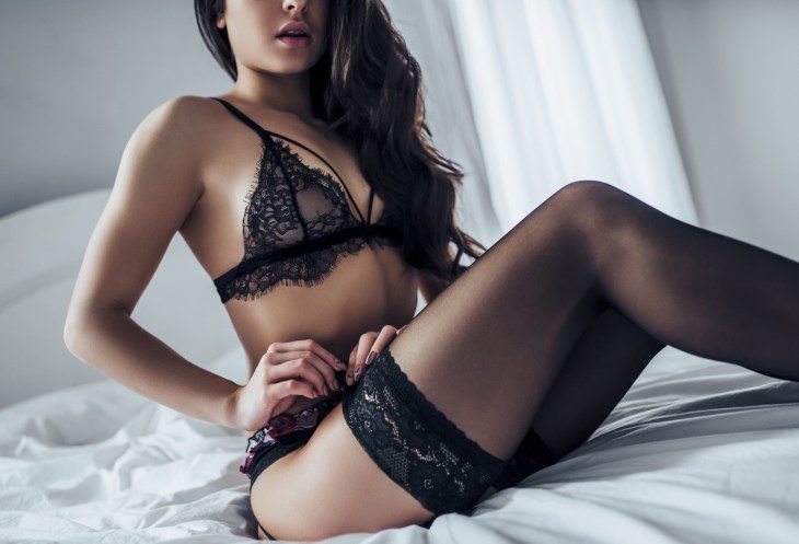Woman on a bed wearing a matching set of black lace lingerie