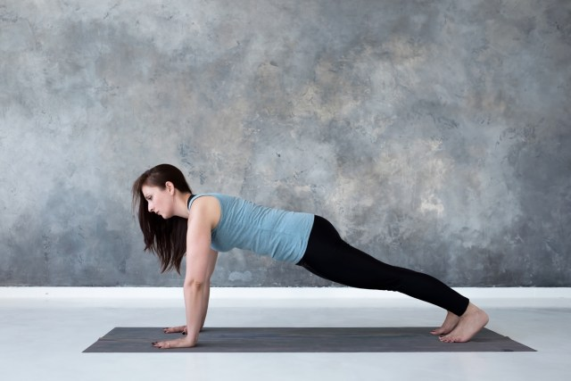 Woman practicing plank pose on her yoga mat