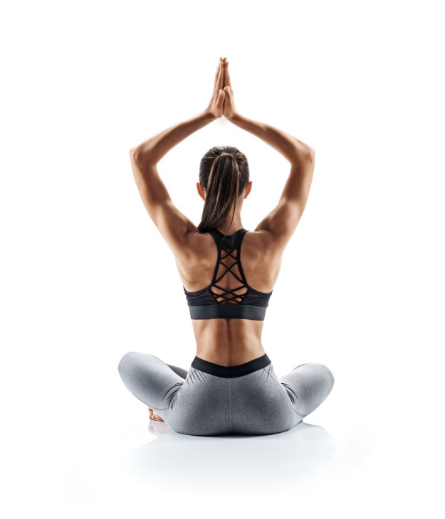 woman's back to the camera sitting doing a yoga pose
