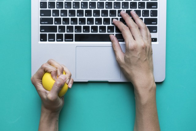 turquoise background pair of hands one is squeezing a stress ball the other types on a laptop computer