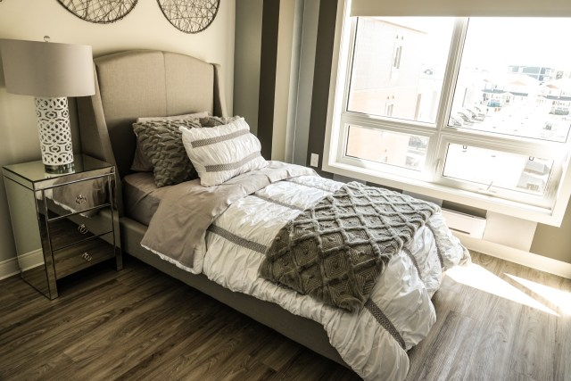 Twin size bed with white and grey bedding