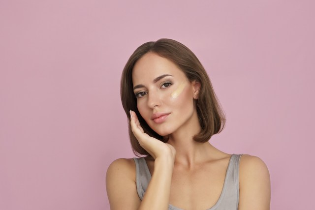 cosmetic foundation on skin on pink background