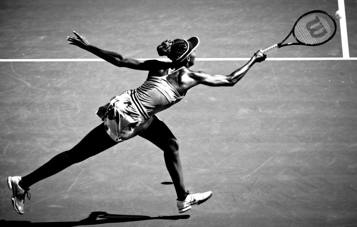 black and white photo of venus playing tennis on field