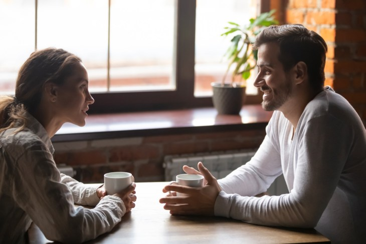 Side view smiling biracial woman sitting at table in cafe with caucasian man couple talking in cozy coffeeshop drinking tea coffee.