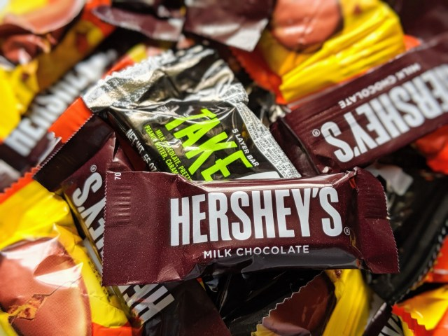 Hershey's mini chocolate bar against a background of assorted Hershey's candy bars.