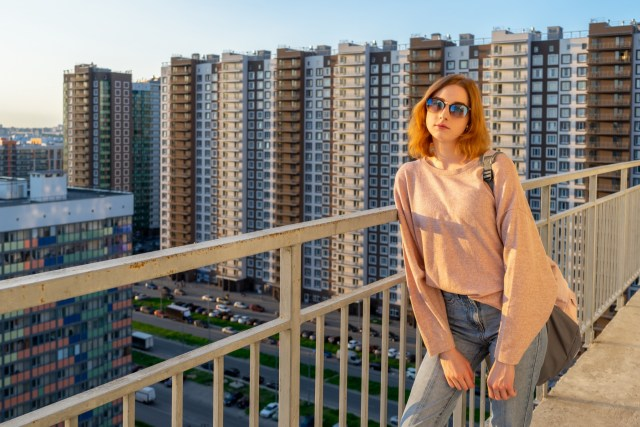 Tween redhead girl in pullover, jeans and sunglasses standing on balcony against high-rise multi-storey residential building at sunset.