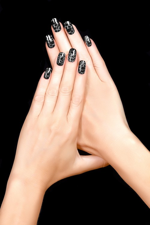 Trendy crackle nail polish in black. Manicure and nail tattoo trend. Closeup of woman hands isolated on black background