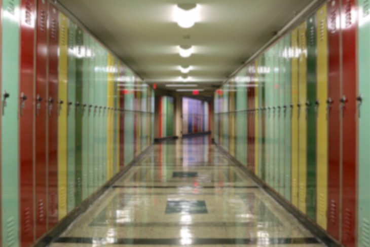 Blurred background of tunnel-like hallway lined with multi-colored lockers.
