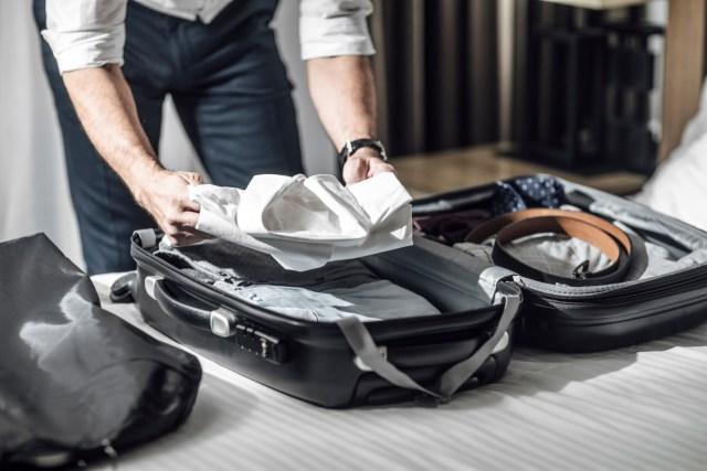 Hands of unrecognisable businessman packing his shirts in suitcase for business travel.