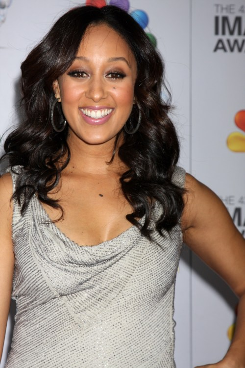 Tamera Mowry-Housley smiling in silver sleeveless dress hair down