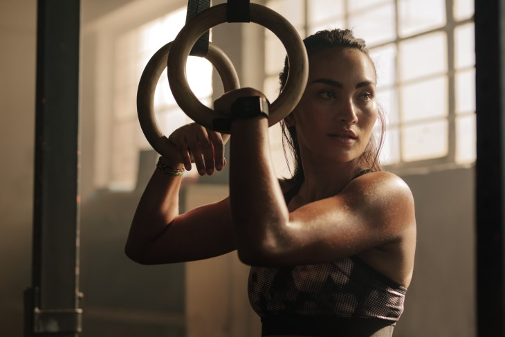 Exercising woman holding gymnast rings