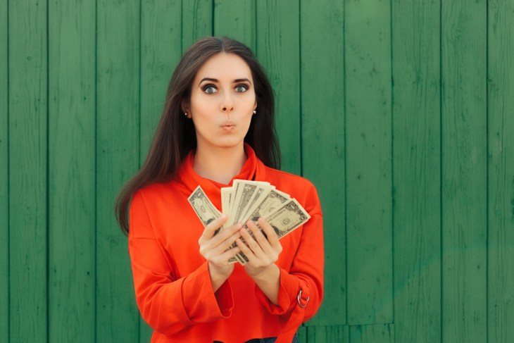 Funny Casual Girl Holding Money Thinking to Invest. Successful woman with lots of cash from lucky win.