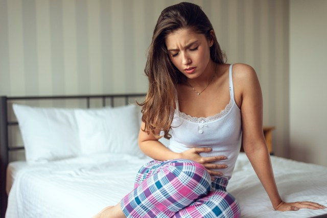woman have a stomachache in bedroom because menstruation