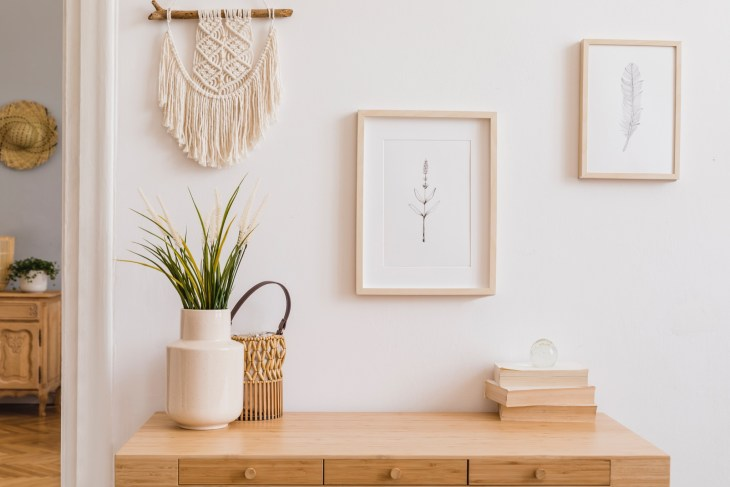 Stylish and modern boho interior of living room with mock up photo frames, flowers in vase, wooden desk, beige macrame and elegant accessories. Design home decor. Bohemian concept.