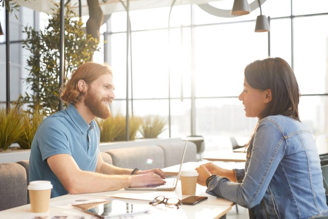 Young bearded businessman talking to young businesswoman