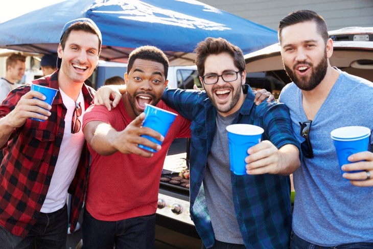 Group Of Male Sports Fans Tailgating In Stadium Car Park