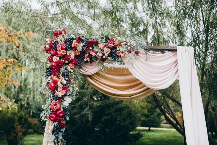 Wedding autumn decor with apples, pomegranate and roses.