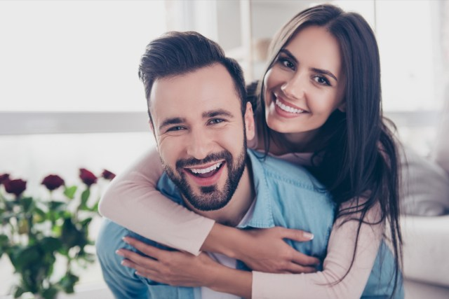 Close up photo of cheerful excited glad careless happy with toothy beaming smile brunette attractive woman and with stylish hairdo man, she is hugging him from the back.