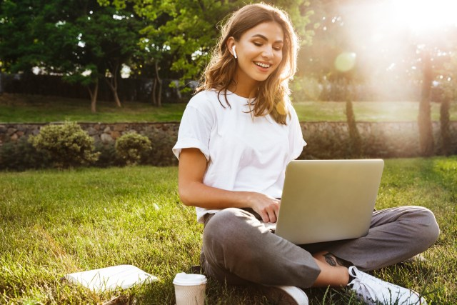 Portrait of pretty young woman sitting on green grass in park with legs crossed during summer day while using laptop and wireless earphone for video call.