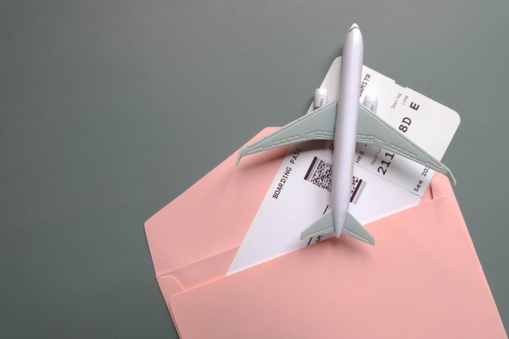Boarding pass in gift pouch with toy airplane.