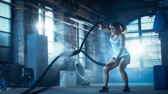 Woman in gym doing high intensity interval training with exercise ropes.