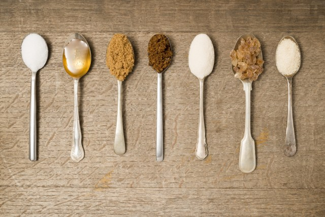 Spoons full of variety of sweetness against wood background.
