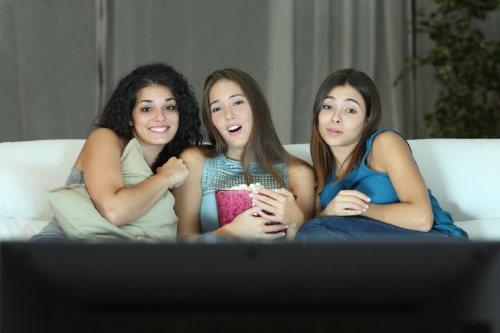 Three friends watching romantic movie on tv sitting on a couch at home