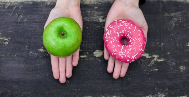 Two hands, one holding a green apple, the other holding a pink donut.