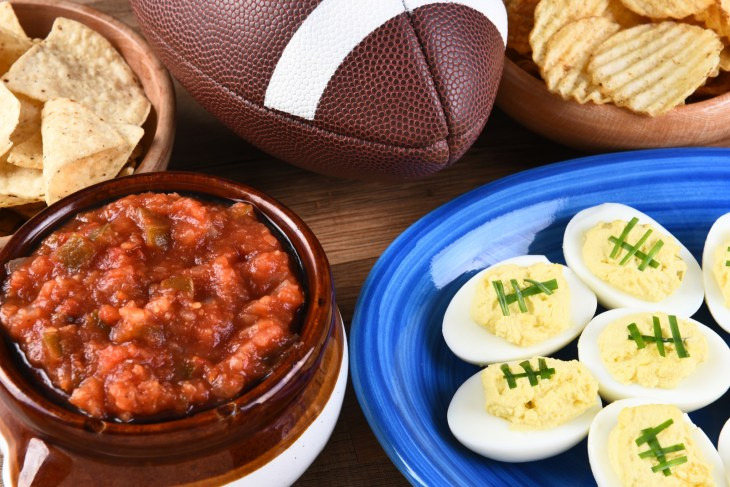 Football, salsa, chips, deviled eggs, and chips on table.