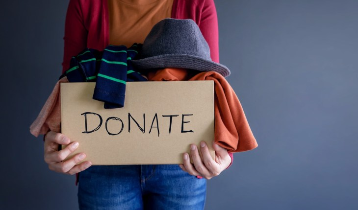 Person holding donation box full of clothes