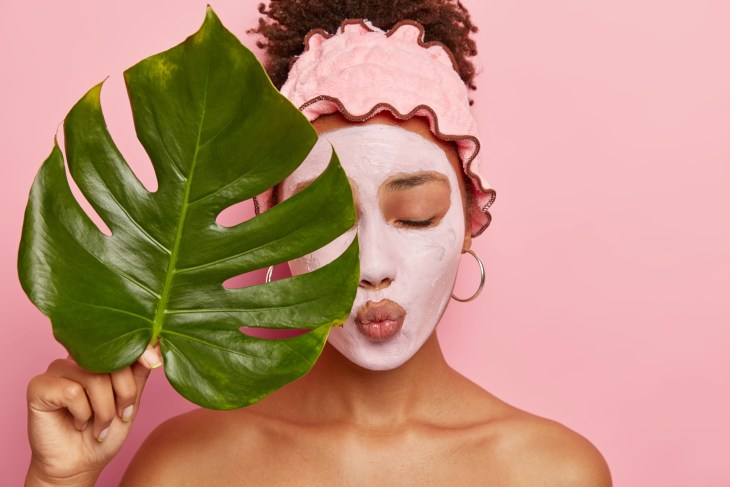 young Afro American woman applies nourishing clay mask, has eyes shut, lips folded, covers half of face with big green leaf