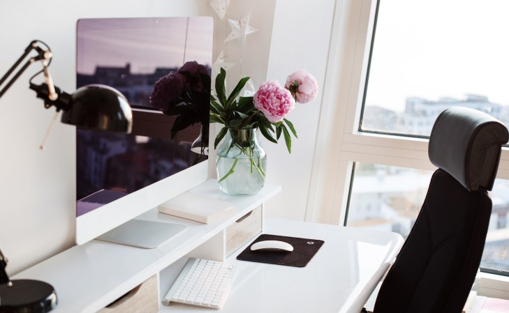Workplace. Office. Scandinavian interior. Presentation template. Flowers, keyboard, computer, desk, desk lamp. Pink peonies in vase. White desk. Home office interior. View from window.
