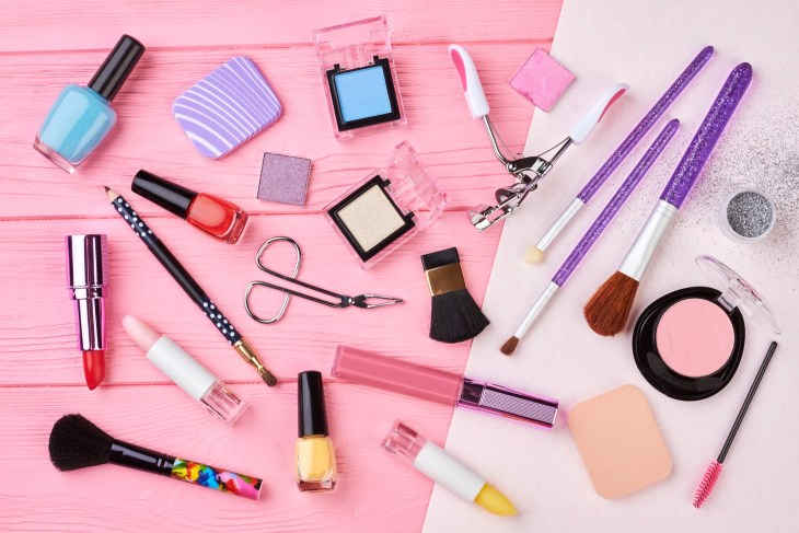 Female cosmetics products set, top view. Makeup cosmetics, brushes and other essentials on pink background.