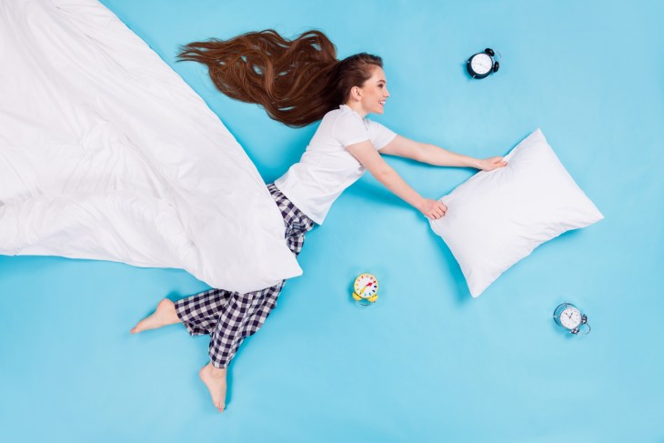 lady lying flying hold blanket big pillow having fun alarm clock wear t-shirt pants pajama isolated blue color background