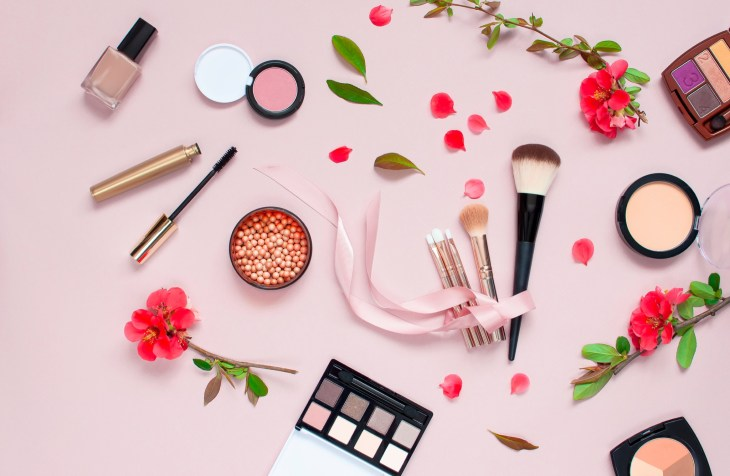 Various cosmetic products for make-up with red flowers on a pink background